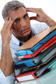 Man with stacks of paperwork — Stock Photo