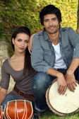 Couple in the park with bongo drums — Stock Photo