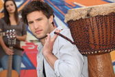 Young man carrying a djembe — Foto Stock