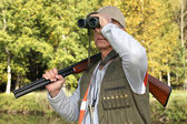 Cazador con rifle mirando a través de binoculares — Foto de Stock