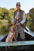 Hunter with dog on boat — Stock Photo