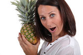 Portrait of a woman holding a pineapple — Stock Photo