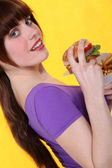 Oblique image of girl with burger — Stock Photo