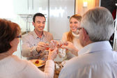 Four adults making a toast at dinner — Stock Photo
