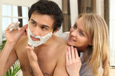 Woman looking at man shaving — 图库照片