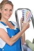 A woman wearing dungarees and showing us a range of colors. — Stock Photo