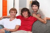 Three young men on sofa — Stock Photo