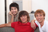 Three male students gathered on the sofa — Stock Photo