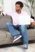 Homme à la maison avec un ordinateur portable et le téléphone — Photo