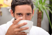 Black man drinking from bowl — Stock Photo