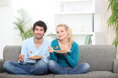 Couple having dinner on their couch — Stock Photo