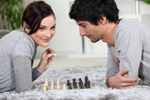 Couple playing chess whilst lying on the carpet — Stock Photo