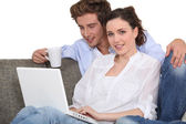 Lovely couple with laptop indoors — Stock Photo
