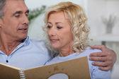 Äldre par tittar på ett fotoalbum — Stockfoto