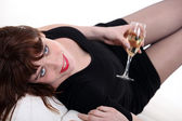 Woman in a little black dress with a glass of champagne — Stock Photo