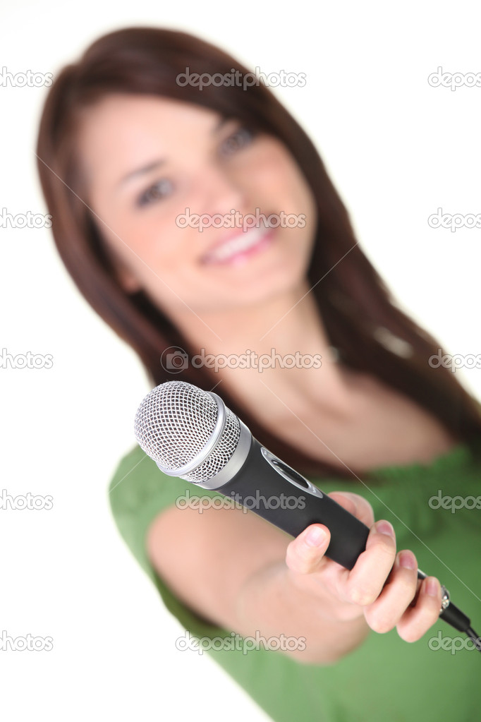 Young woman holding out a microphone — Stock Photo #9741976