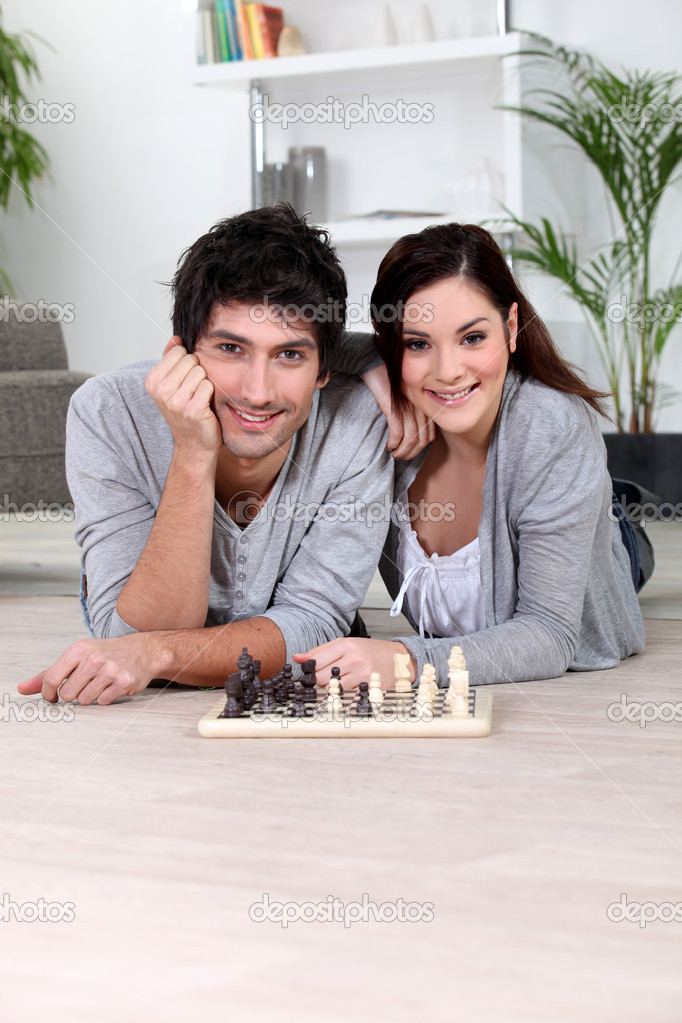 Couple playing chess lying — Stock Photo #9746587