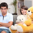 Stock Photo: Young couple with teddy bears on sofa
