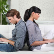 Couple using two laptops on the sofa — Stock Photo #9757860