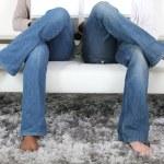 Legs crossed of couple sitting on sofa — Stock Photo