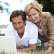 Couple using their laptop in a field — Stock Photo
