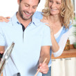 Smiling couple cooking at an electric hob - Stock Photo
