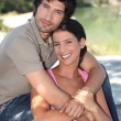 Couple embracing in front of pond — Stock Photo #9759765