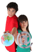 Teens with globe and at sign — Stock Photo