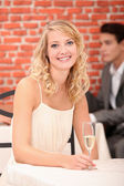 Woman in restaurant with a glass of champagne — Stock Photo
