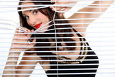 Brunette looking through blinds — Stock Photo