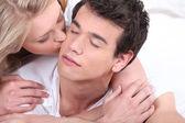 Woman kissing her boyfriend on the cheek — Stock Photo