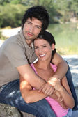 Couple embracing in front of pond — Stock Photo