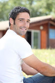 Young man sitting in front of chalet — Stock Photo
