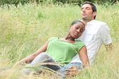 Mixed-race couple relaxing in a field — Stock Photo