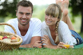Couple having romantic picnic in a field — Stock Photo