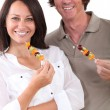 Portrait of couple with fruit brochettes — Stock Photo #9760103