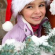 Little girl in Santa hat stood by tree — Stock Photo
