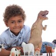 Young boy playing with a toy dinosaur and collection of domestic animals — Stock Photo