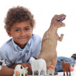 Stock Photo: Young boy playing with toy dinosaur and collection of domestic animals