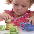 Young girl playing with a tea set — Stock Photo