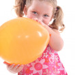 Stock Photo: Young girl in pink flowery dress with yellow balloon