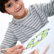 Little boy drawing a circle composed of arrows - Stock Photo