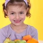 Little girl holding plate of fruit — Stock Photo #9767451