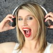 Blonde music fan with piercing in tongue - Stockfoto