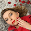 Woman lying surrounded by rose petals — Stock Photo #9767822