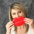 Blond woman holding novelty lips in  front of her face — Stock Photo