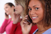A row of women talking on their cellphones — Stock Photo