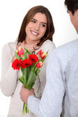 Young romantic guy offering his belle flowers — Stock Photo