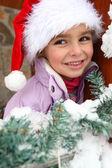 Little girl in Santa hat stood by tree — Stock Photo
