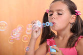 Girl blowing bubbles of soap — Stock Photo